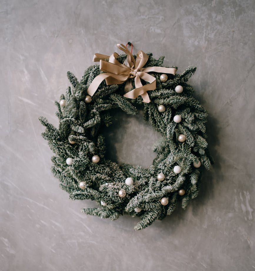 decorative coniferous christmas wreath on wall in room